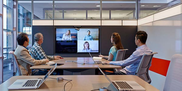 People videoconferencing in a large team studio